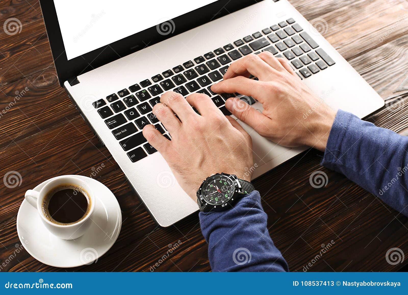 Estudante/blogger/escritor/homem ocasionalmente vestidos que trabalha no portátil do PC, datilografando no teclado, escrevendo o