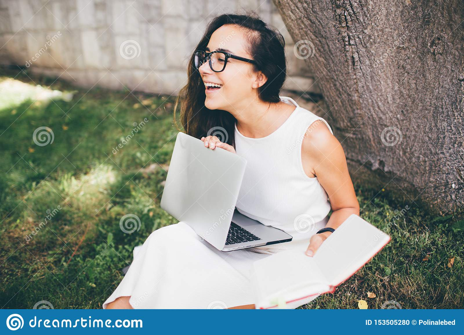 Estudante bonita que aprende suas lições que sentam-se na grama