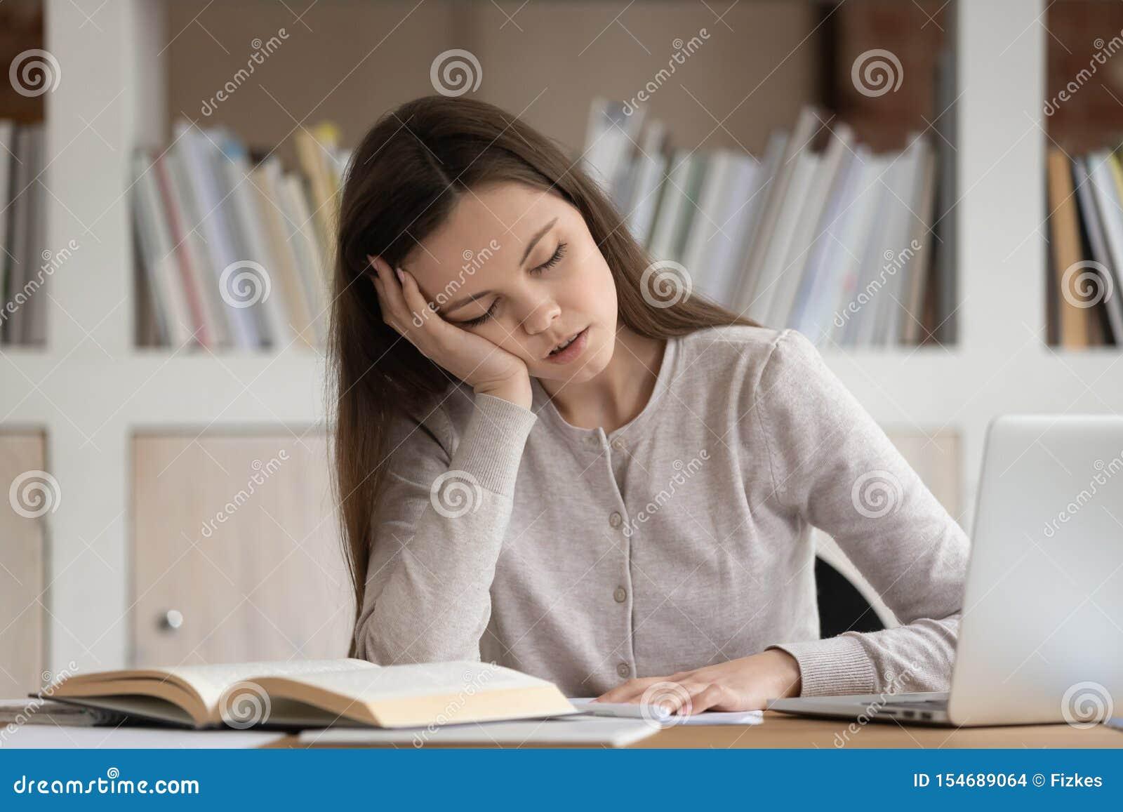 A estudante cansada cai estudo adormecido no local de trabalho