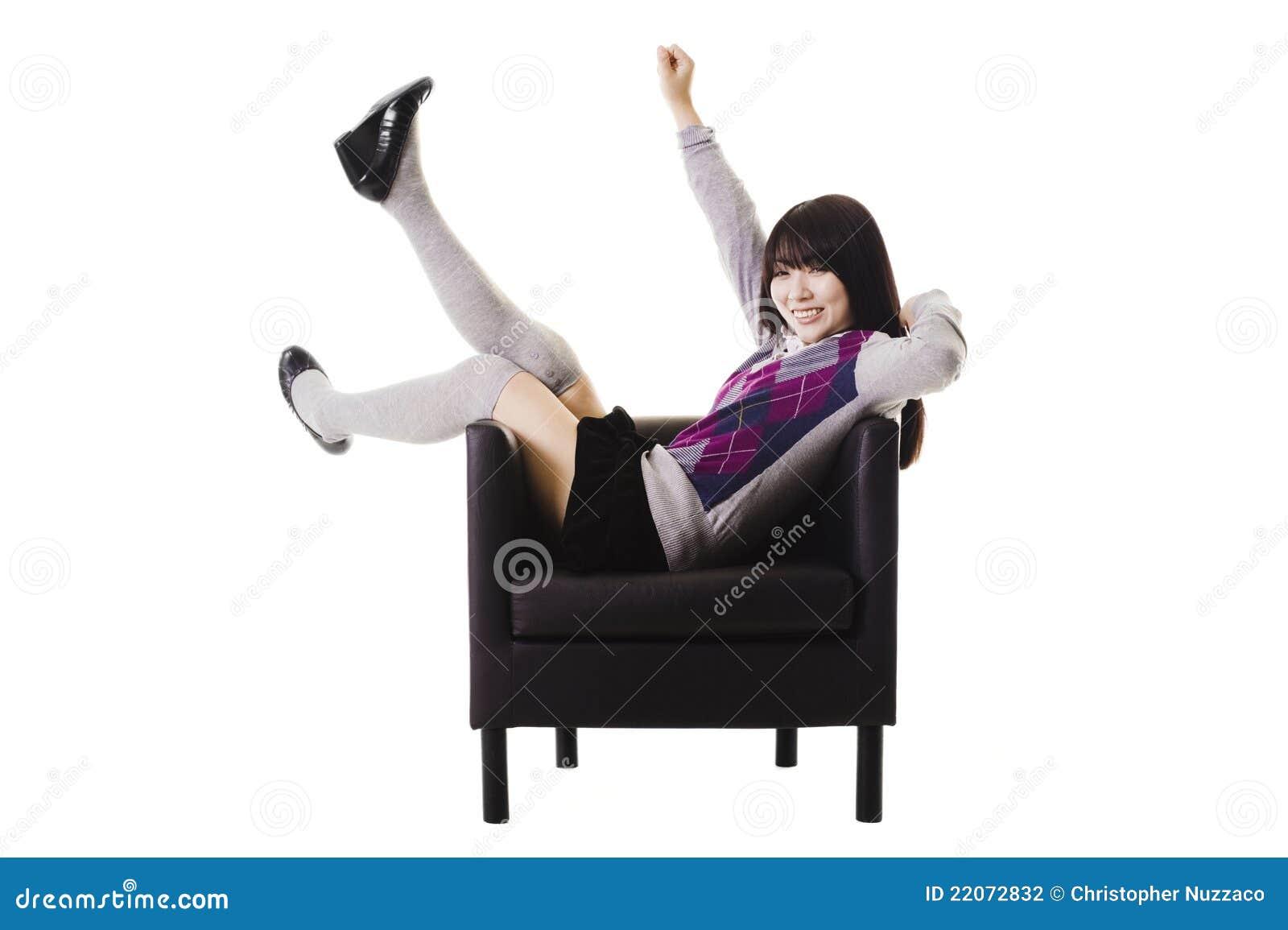 Estudante chinês Excited em uma cadeira de couro.