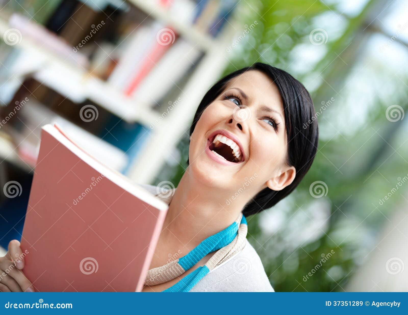 Estudante com o livro na biblioteca