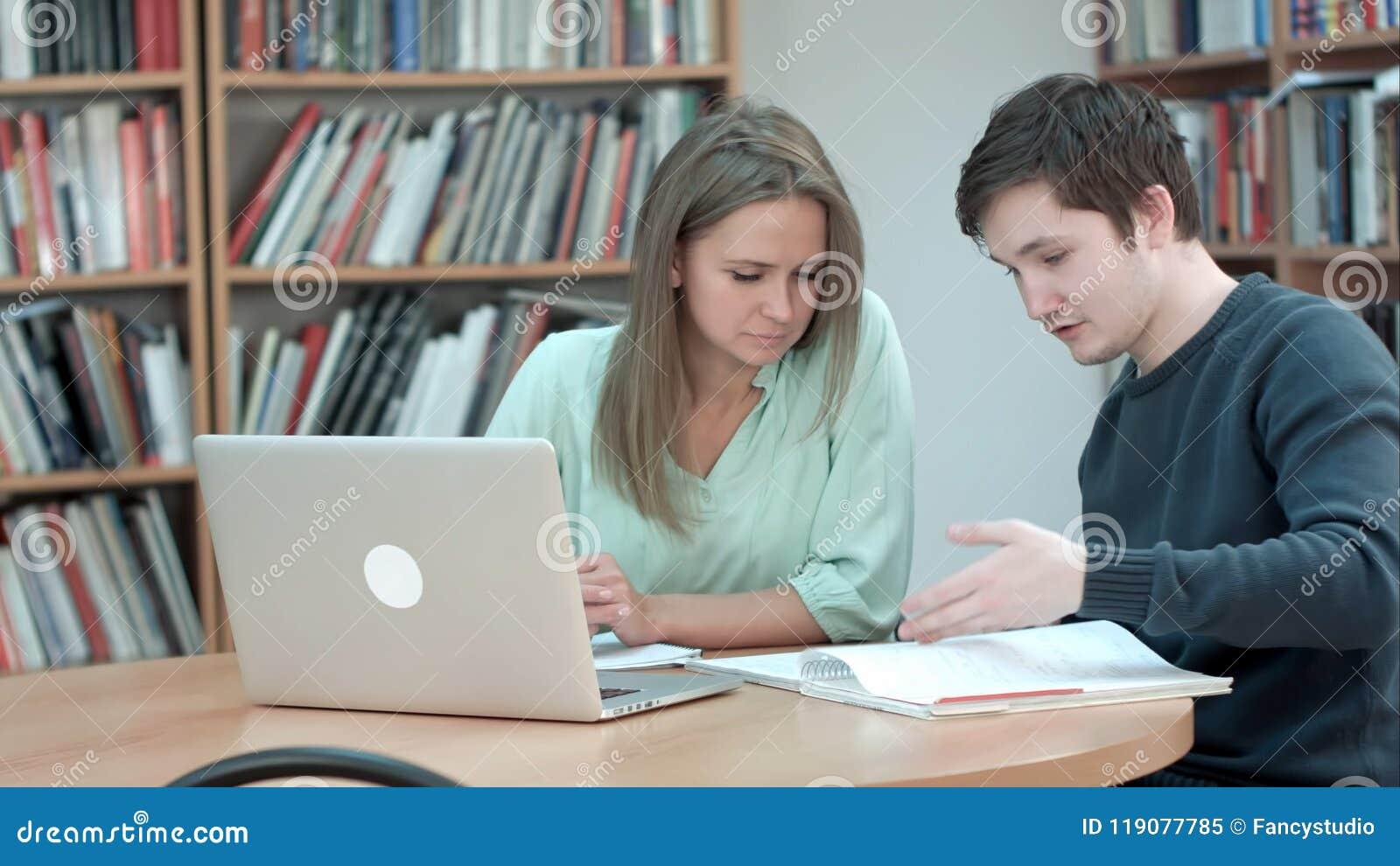 Estudante da High School que trabalha na biblioteca após classes, usando o portátil
