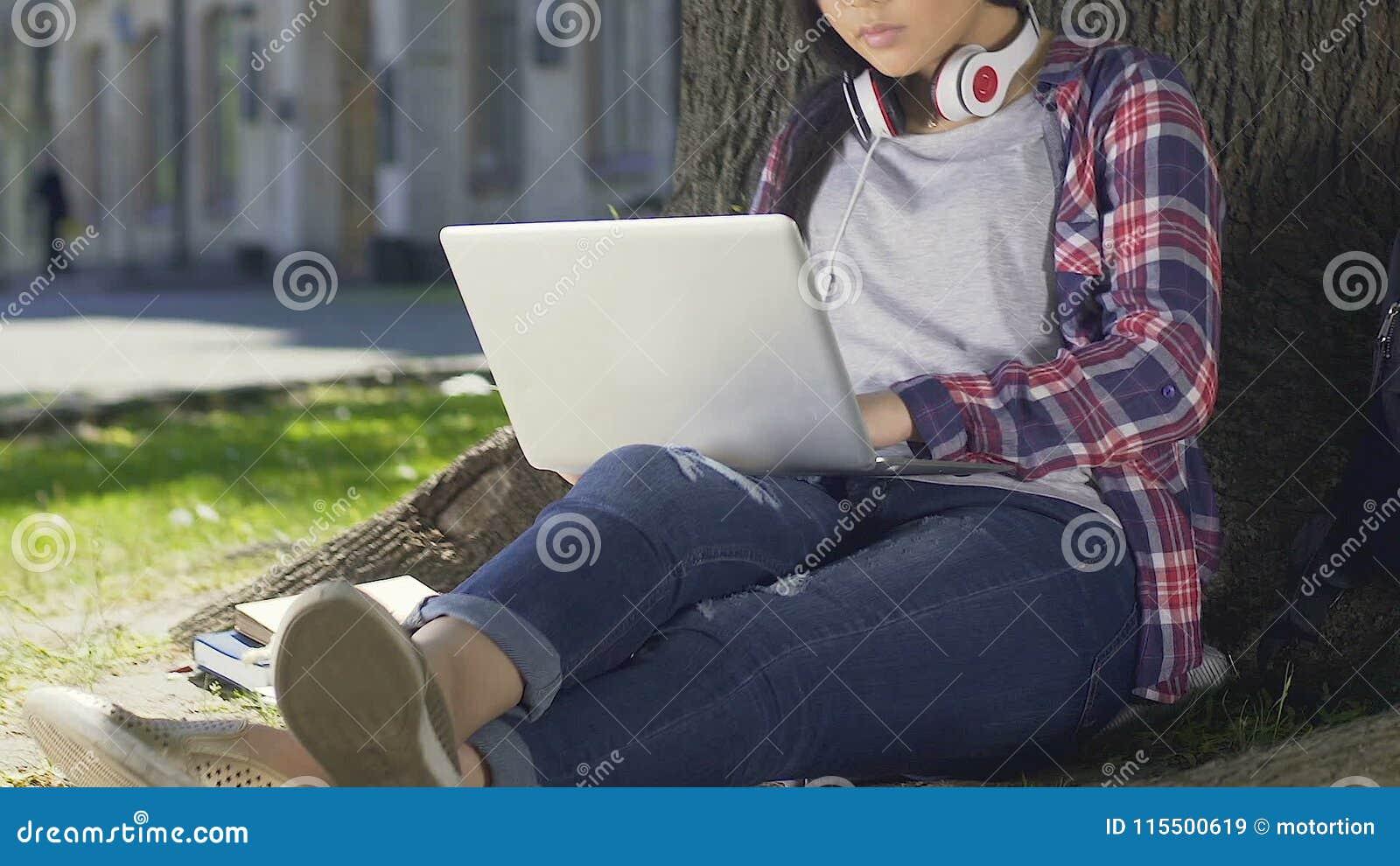 estudante da Misturado-raça que faz seu projeto do diploma que senta-se com o portátil openair video estoque