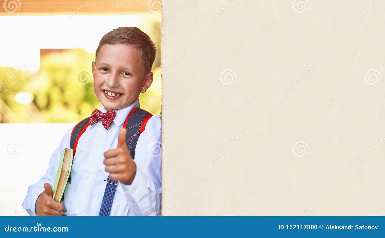 A estudante do menino que guarda um livro de texto que inclina-se contra a parede da escola mostra um sinal da mão da aprovação q