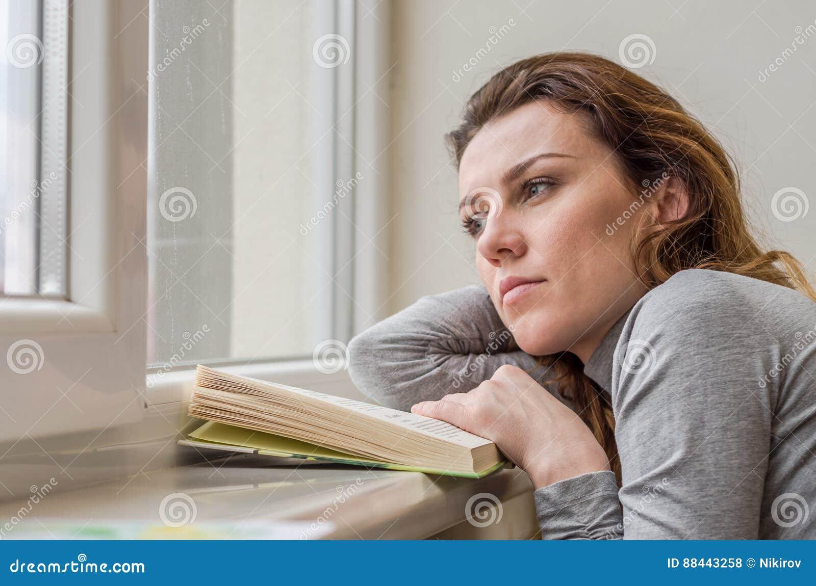 Estudante encantador nova, com o cabelo longo, triste no livro de leitura da janela com lições