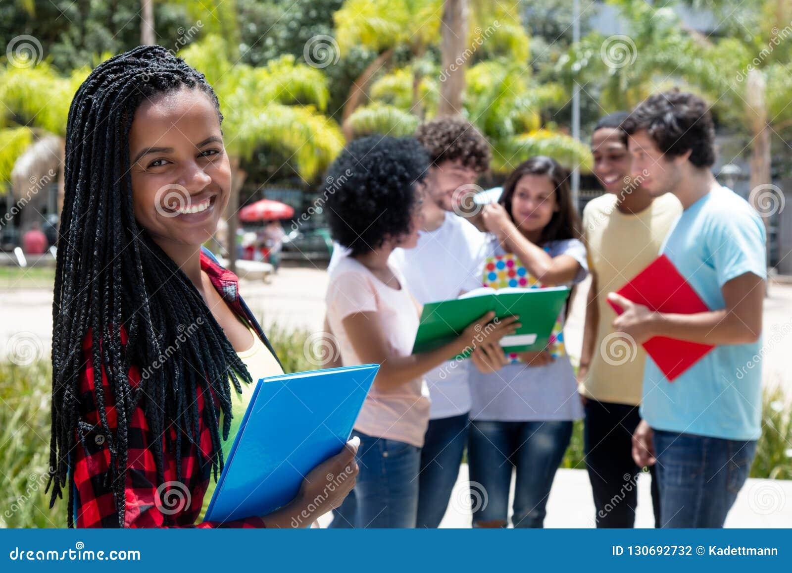 Estudante fêmea africano de riso com grupo de estudantes