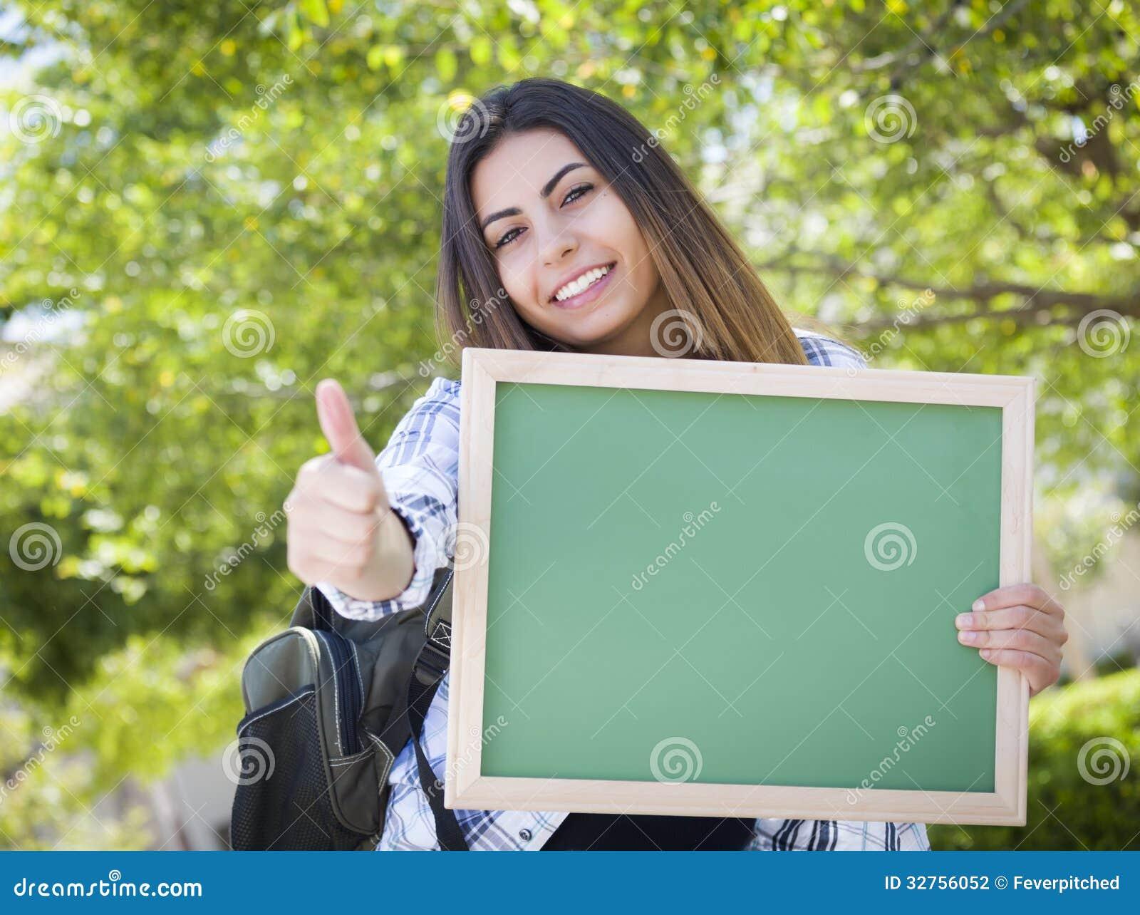 Estudante fêmea entusiasmado Holding Blank Chalkboard de raça misturada