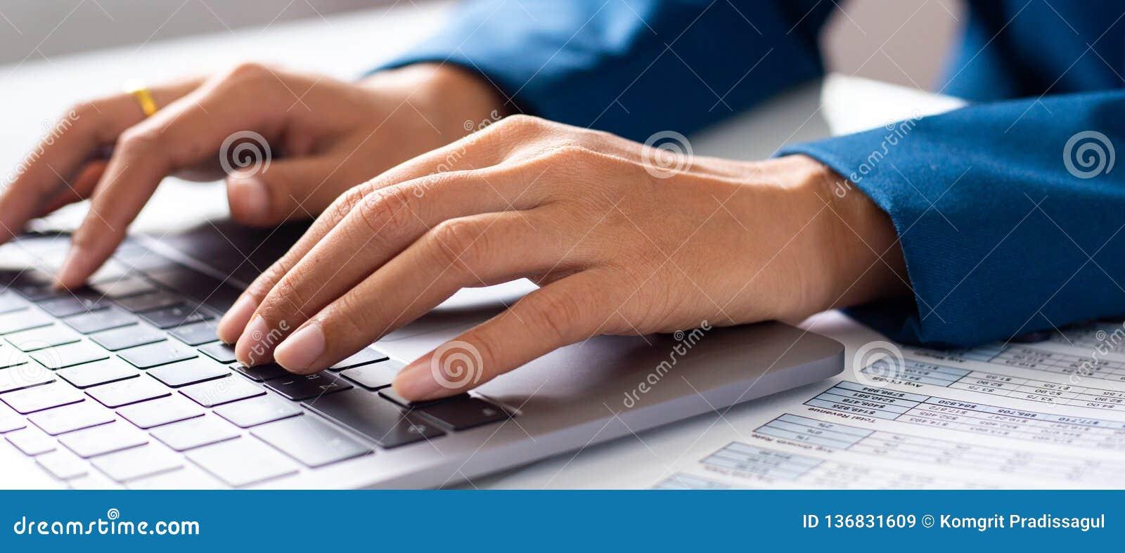Estudante fêmea novo que datilografa no computador que senta-se na tabela de madeira