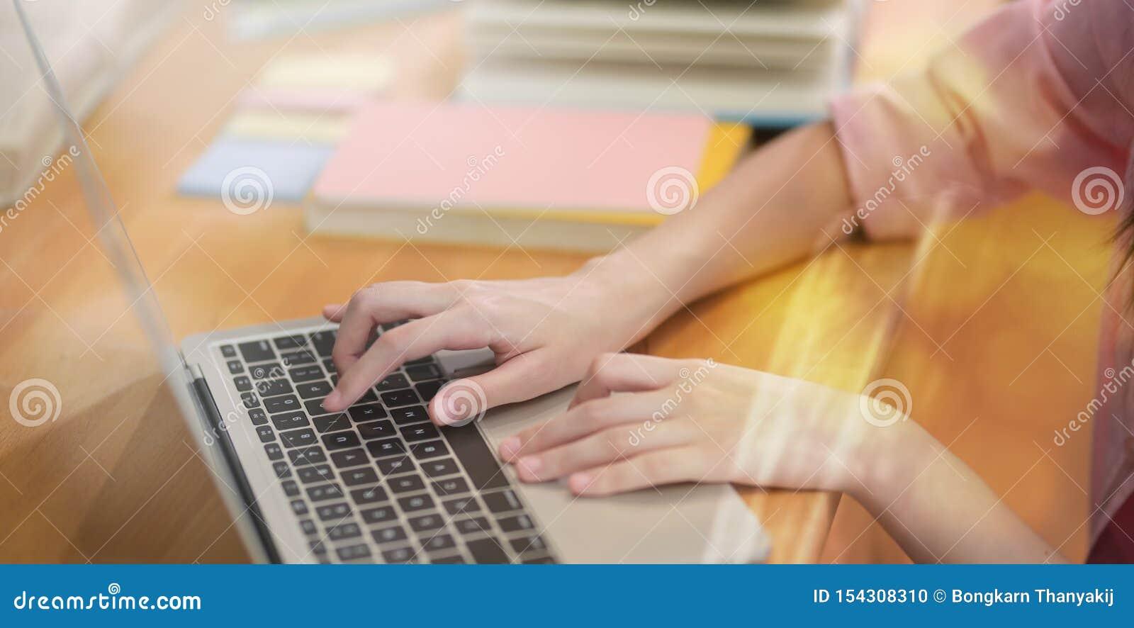 Estudante fêmea novo que datilografa no teclado do portátil