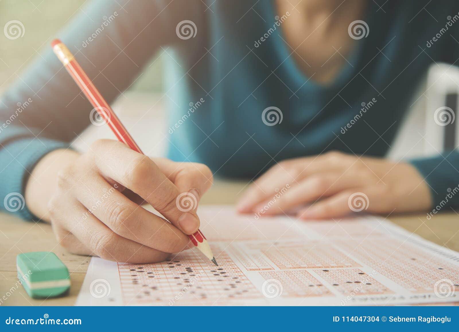 Estudante fêmea que guarda o lápis e o papel de exame