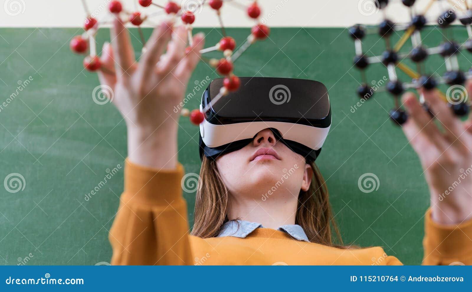 Estudante fêmea que veste os vidros da realidade virtual, guardando o modelo de estrutura molecular Classe da ciência, educação,