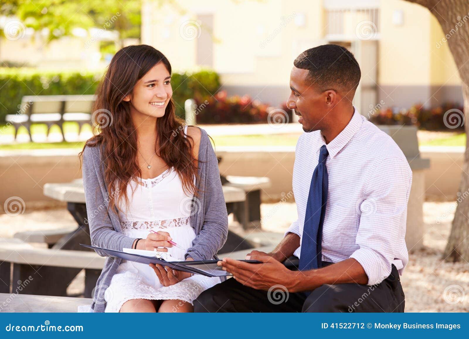Estudante fêmea With Work de Sitting Outdoors Helping do professor