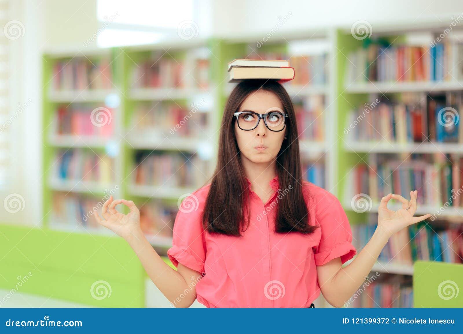 Estudante fêmea Writing uma atribuição do ensaio na biblioteca escolar