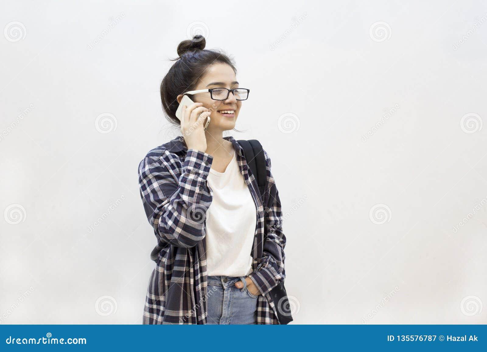 Estudante feliz que fala pelo telefone