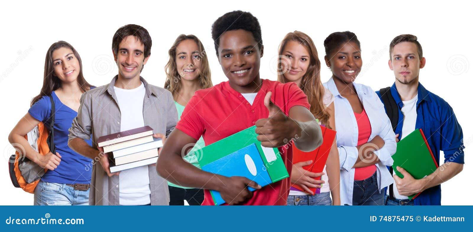 Estudante masculino afro-americano que mostra o polegar com grupo de estudantes