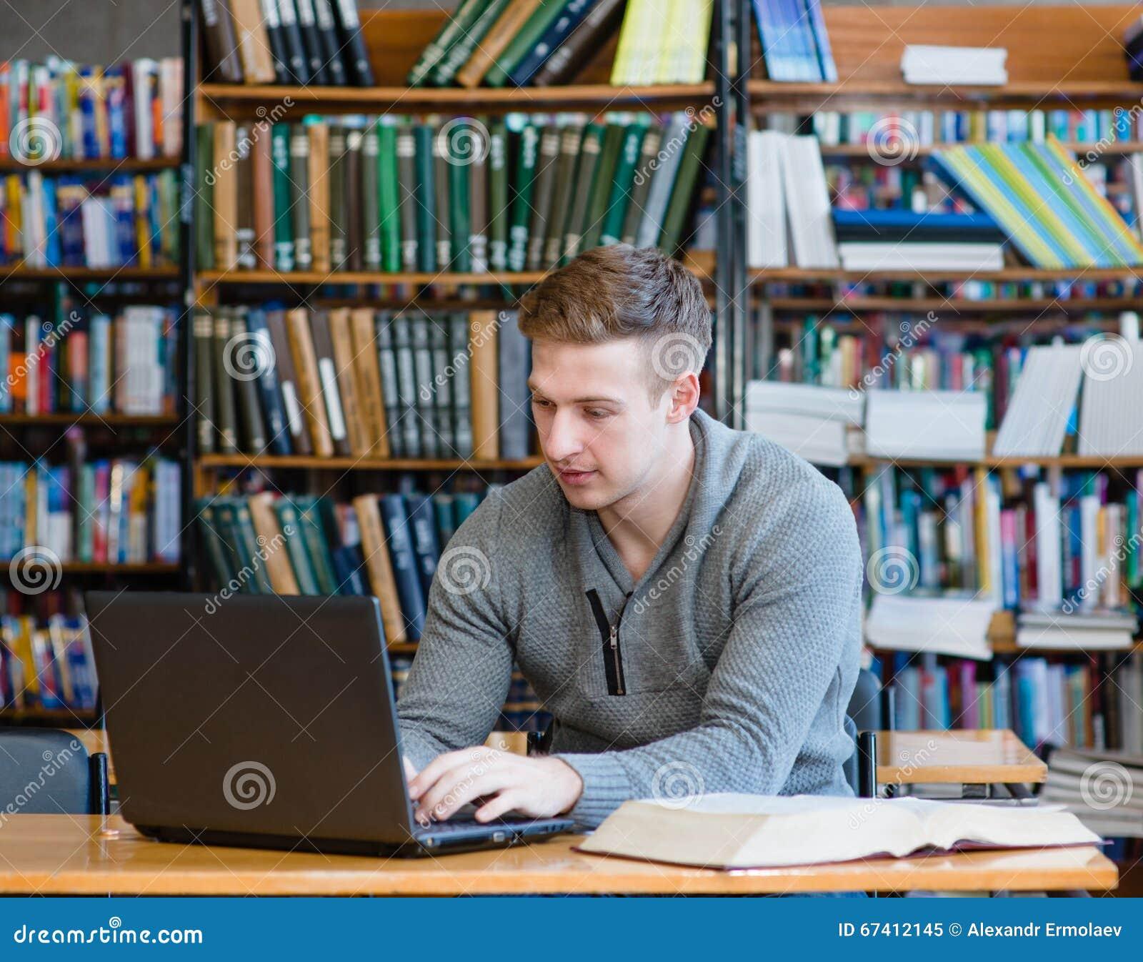Estudante masculino novo que usa o portátil na biblioteca da universidade