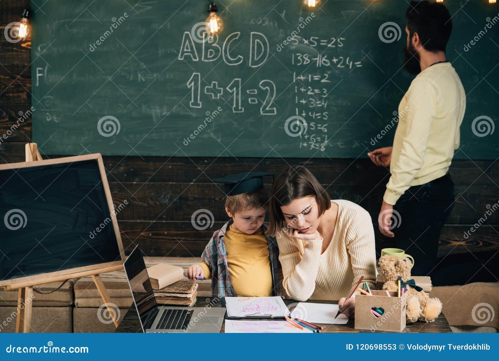 Estudante na classe A estudante aprende o desenho A estudante pequena tem a lição com professor e tutor A estudante desenvolve a