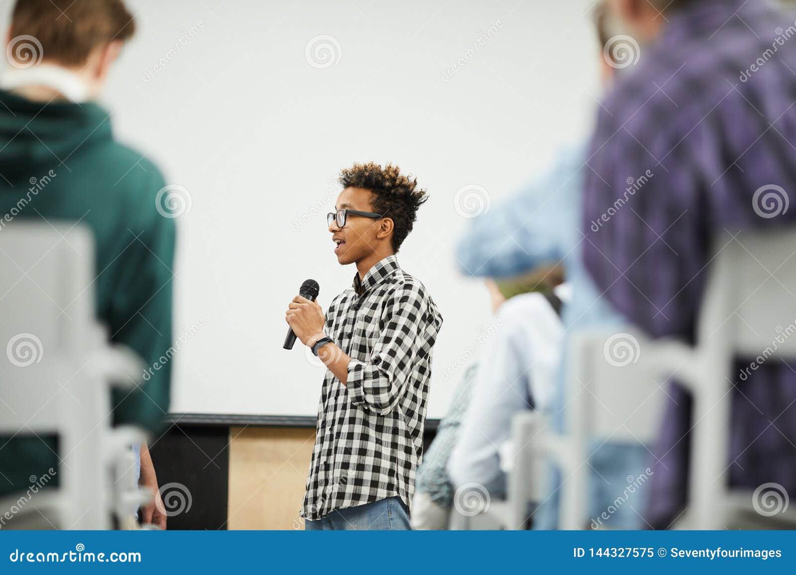 Estudante novo que apresenta seu projeto da partida na conferência
