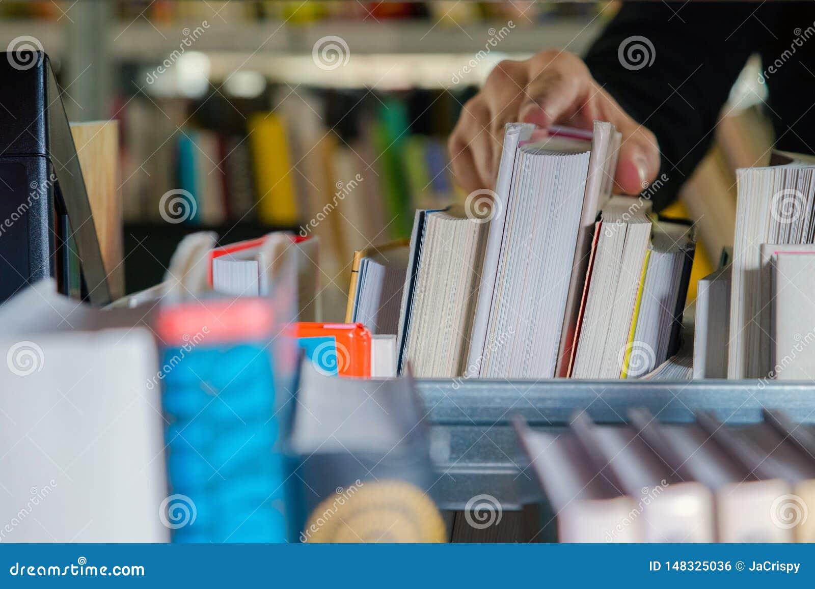 Estudante novo que escolhe um livro da prateleira na biblioteca Preparando-se para exames, homem novo que procura por ou que esco