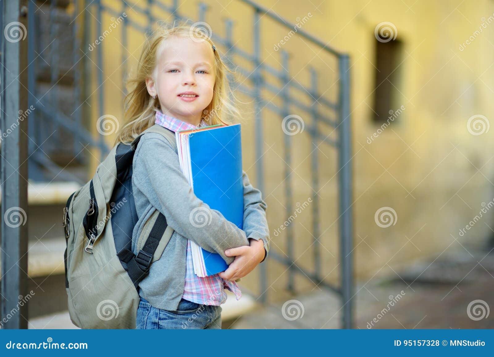 Estudante pequena adorável que estuda fora no dia brilhante do outono Estudante novo que faz seus trabalhos de casa Educação para