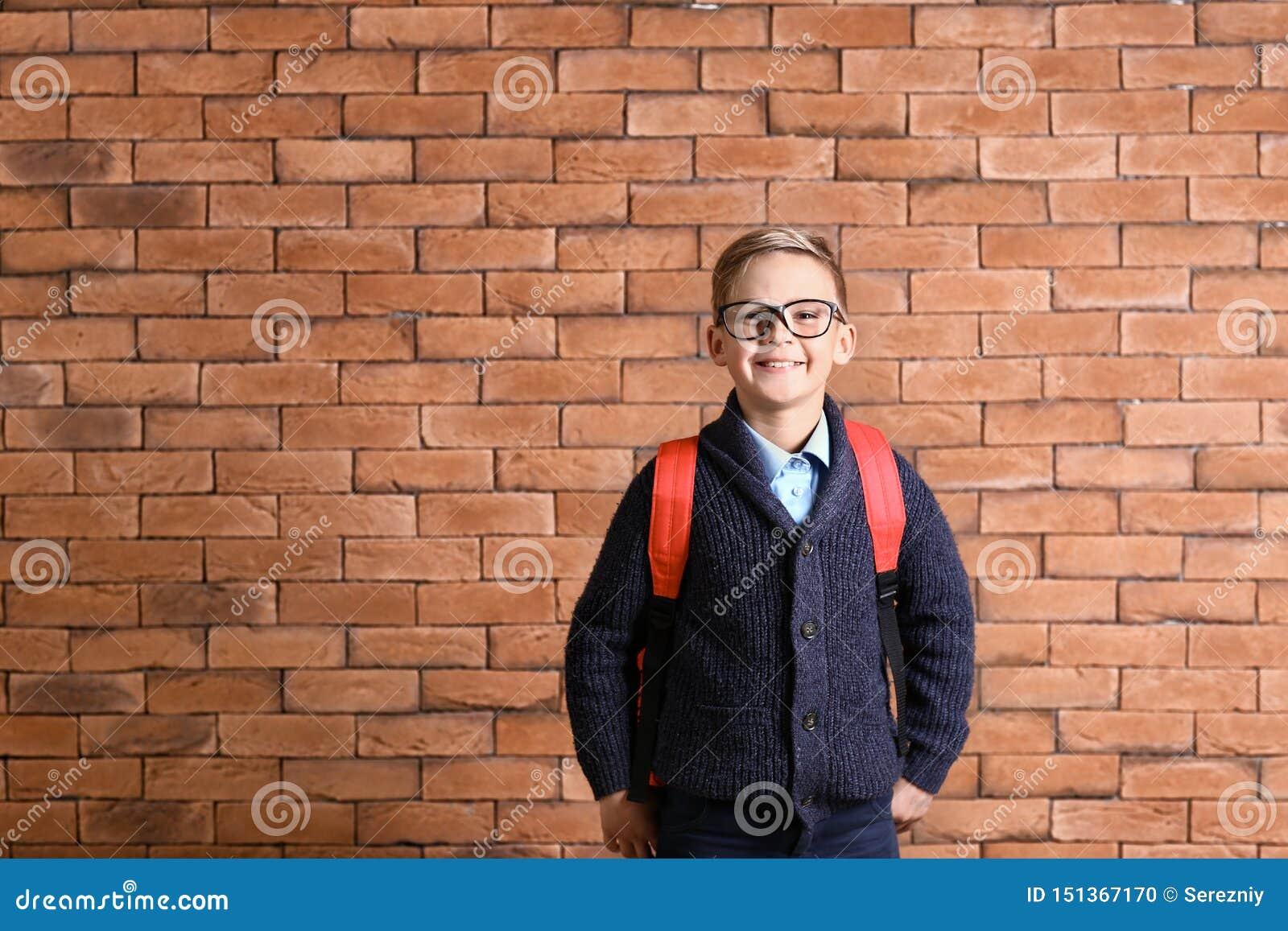 Estudante pequena bonito com a trouxa contra a parede de tijolo