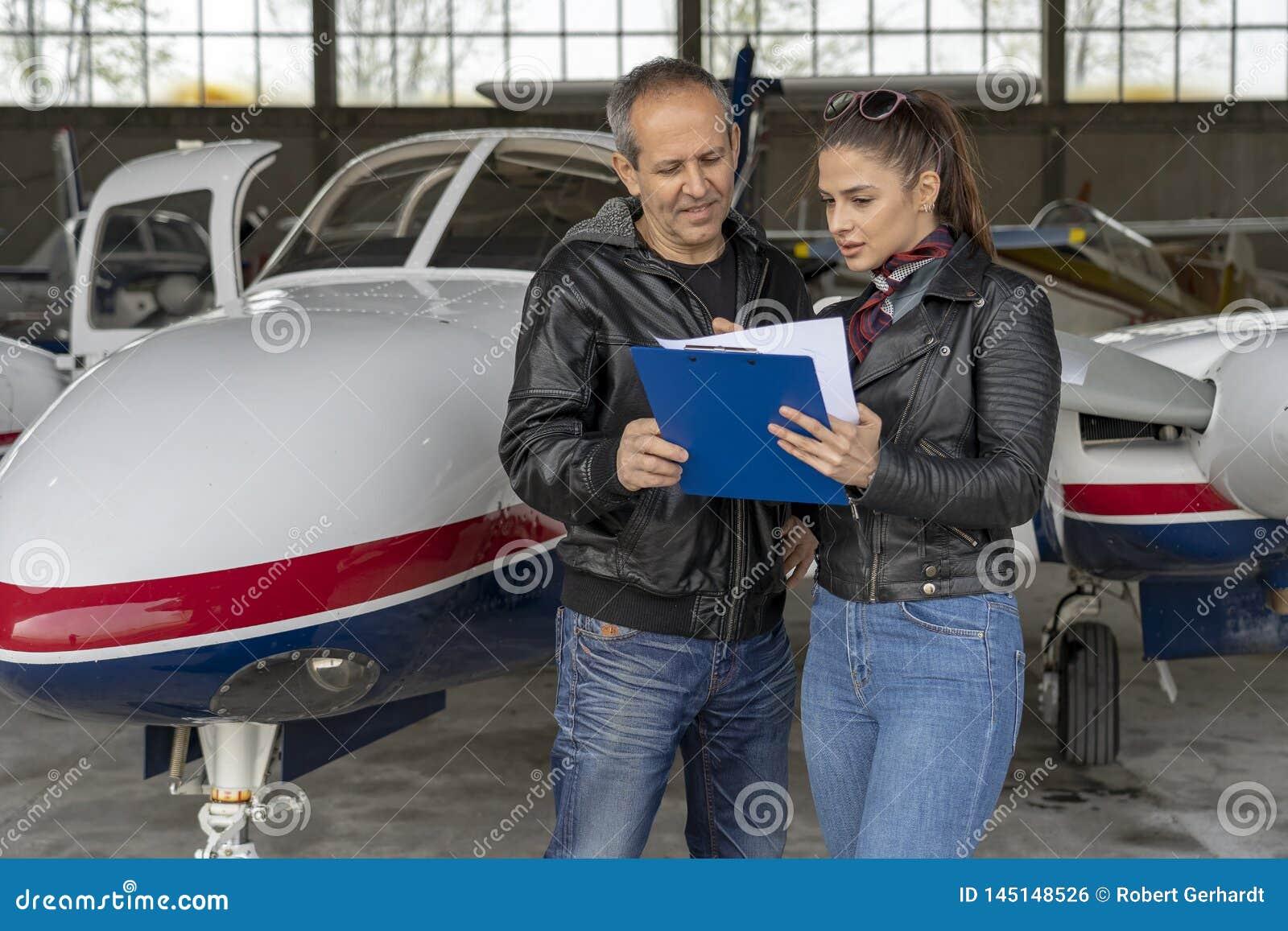 Estudante Pilot e instrutor Going Through um piloto Checklist do Pre-voo