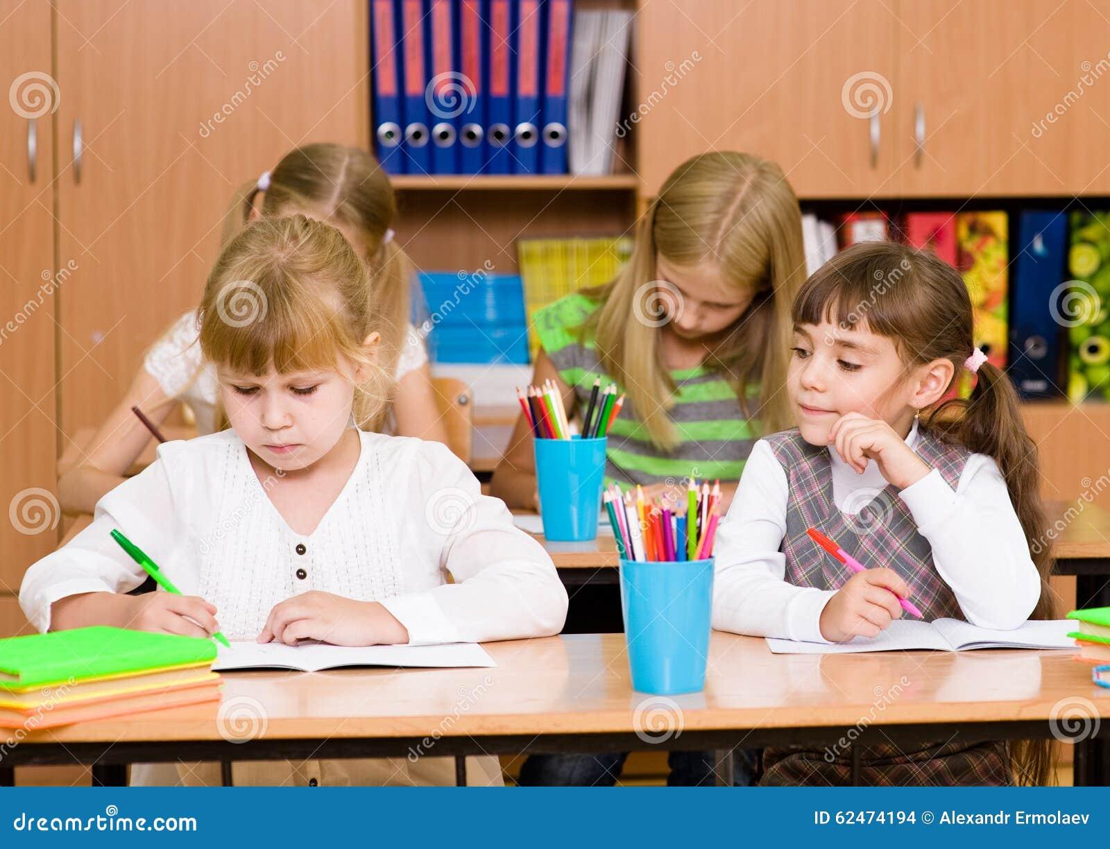 Estudante que engana-se no exame, olhando a escrita de um amigo