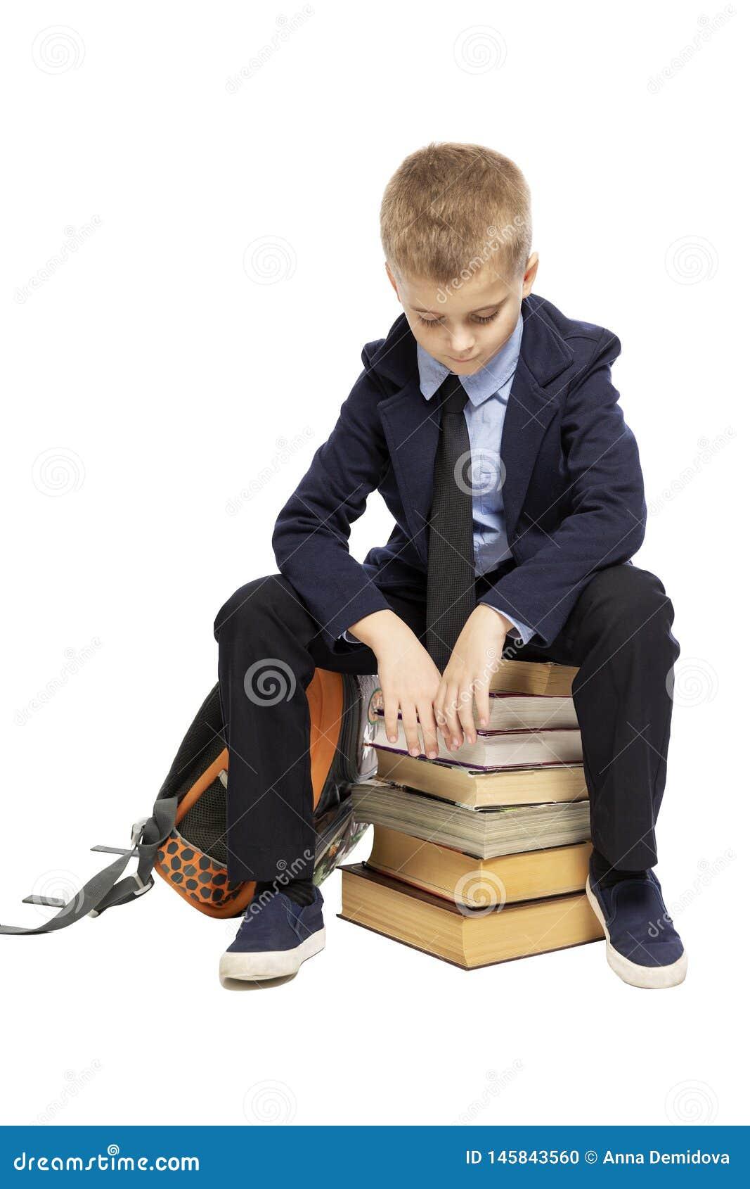 Estudante triste em um terno que senta-se em uma pilha dos livros, cabe?a curvada Isolado em um fundo branco