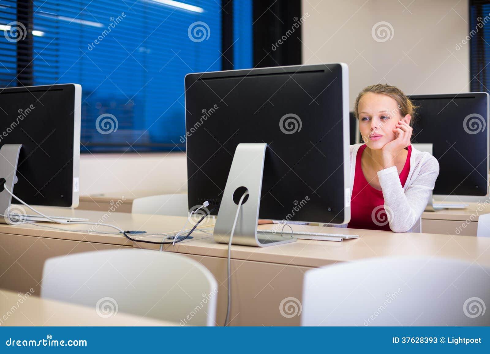 Estudante universitário fêmea bonita, nova que usa um computador de secretária