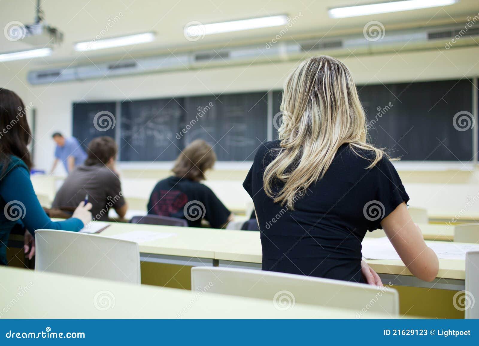 Estudante universitário fêmea que senta-se em uma sala de aula