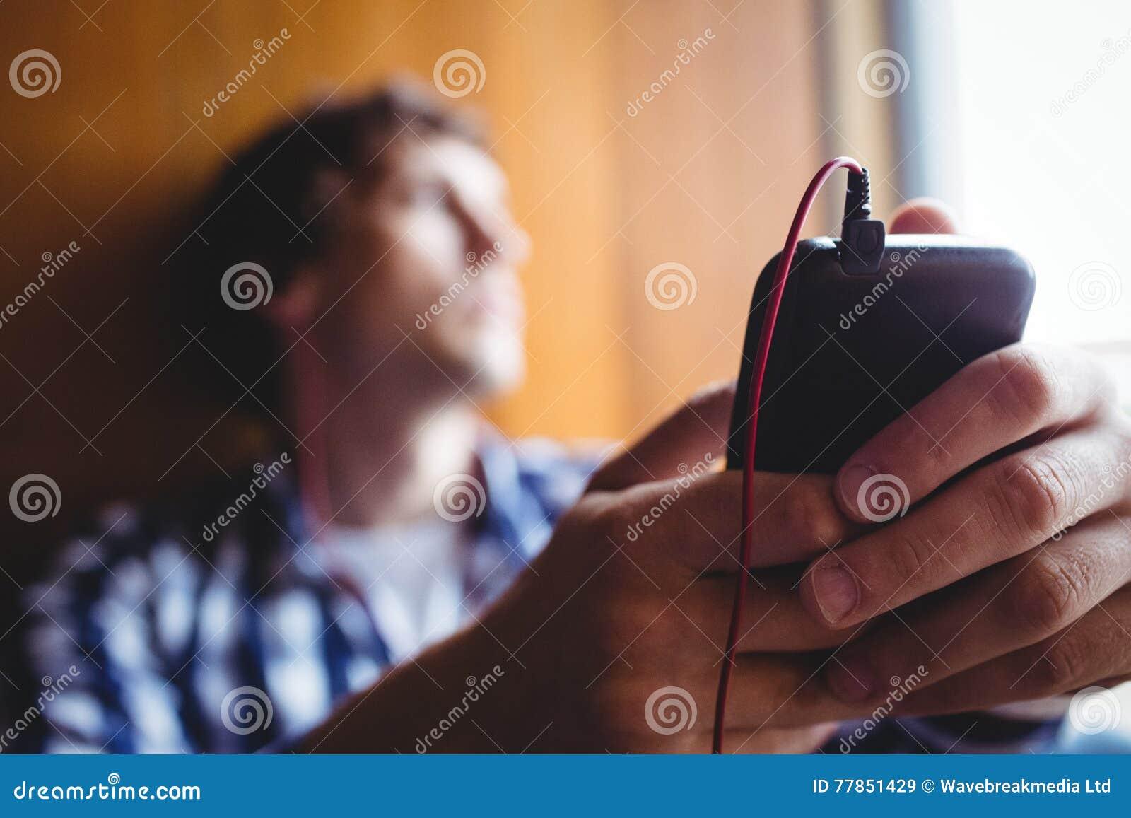 Estudante virado que olha com a janela e a música de escuta