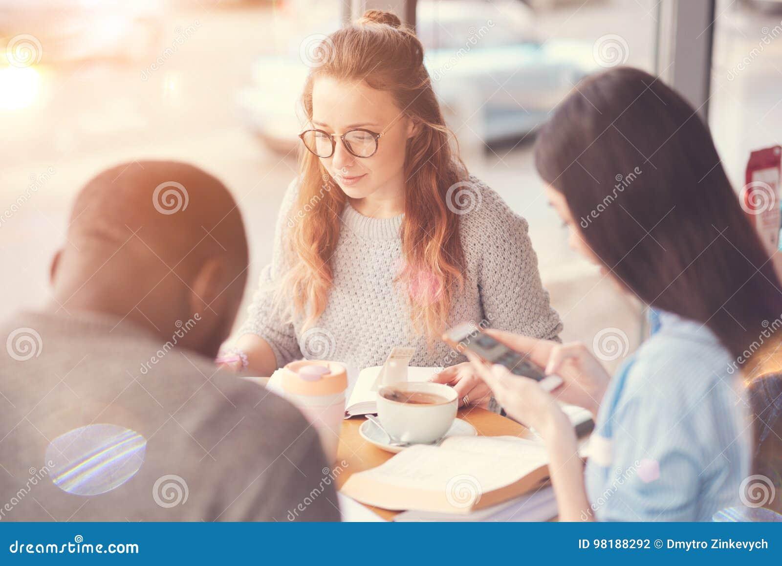 Estudantes agradáveis que sentam-se no café