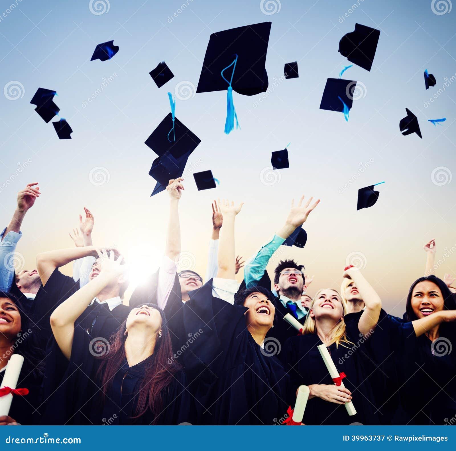 Estudantes alegres que jogam tampões da graduação no ar