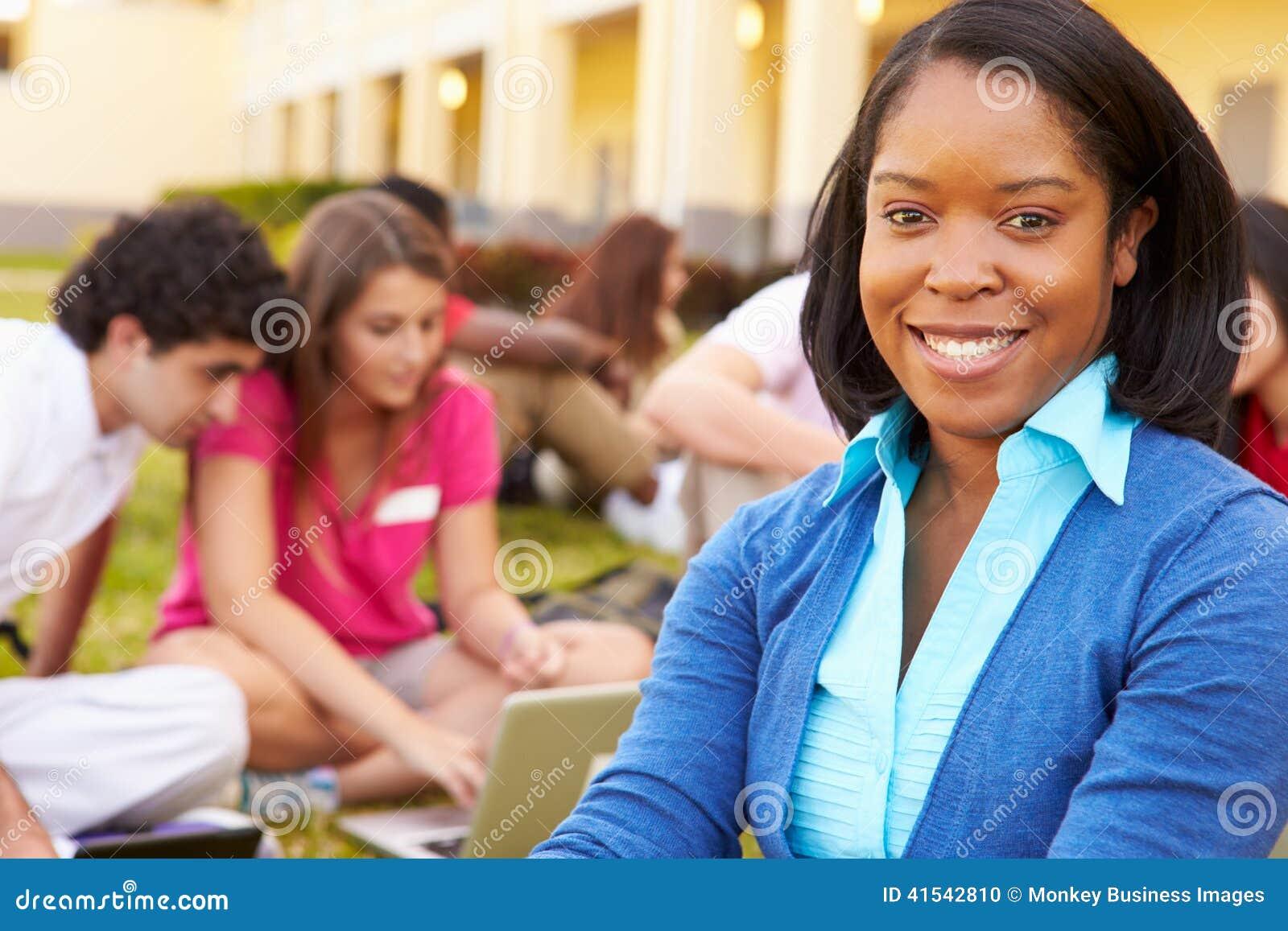 Estudantes altos de Sitting Outdoors With do professor no terreno