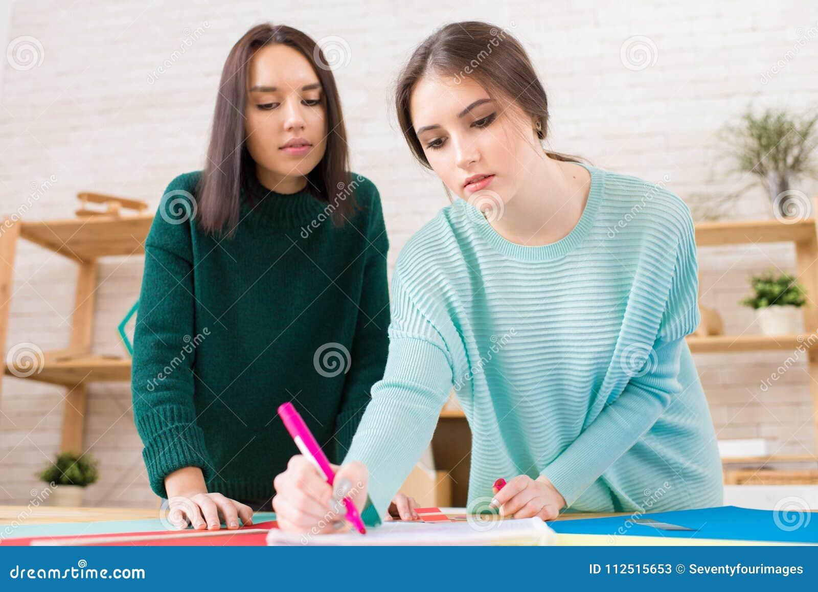 Estudantes bonitos que trabalham no projeto da universidade