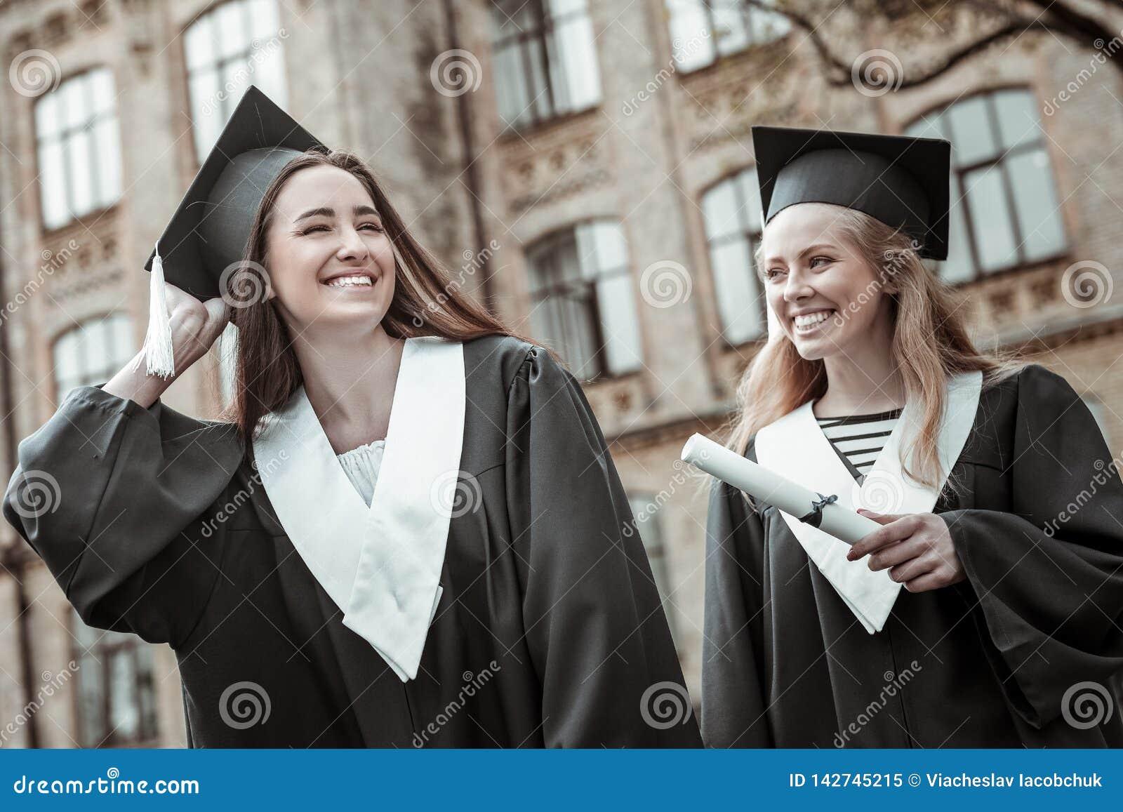 Estudantes bonitos satisfeitos que vestem o uniforme preto da graduação