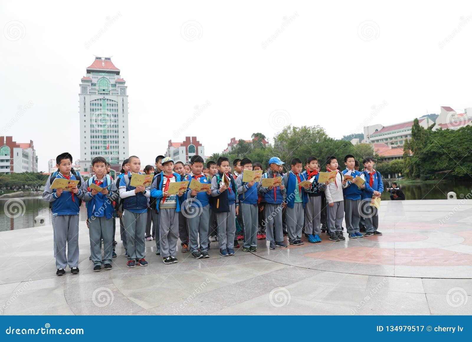 Estudantes chineses asiáticos que leem um livro Nove, foco