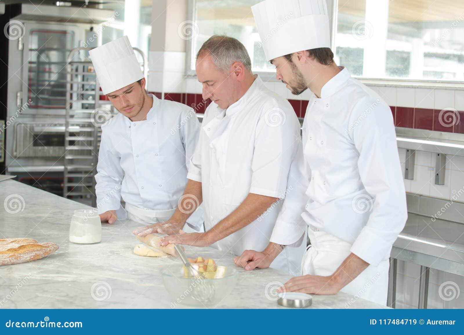 Estudantes culinários que aprendem como misturar a massa na cozinha