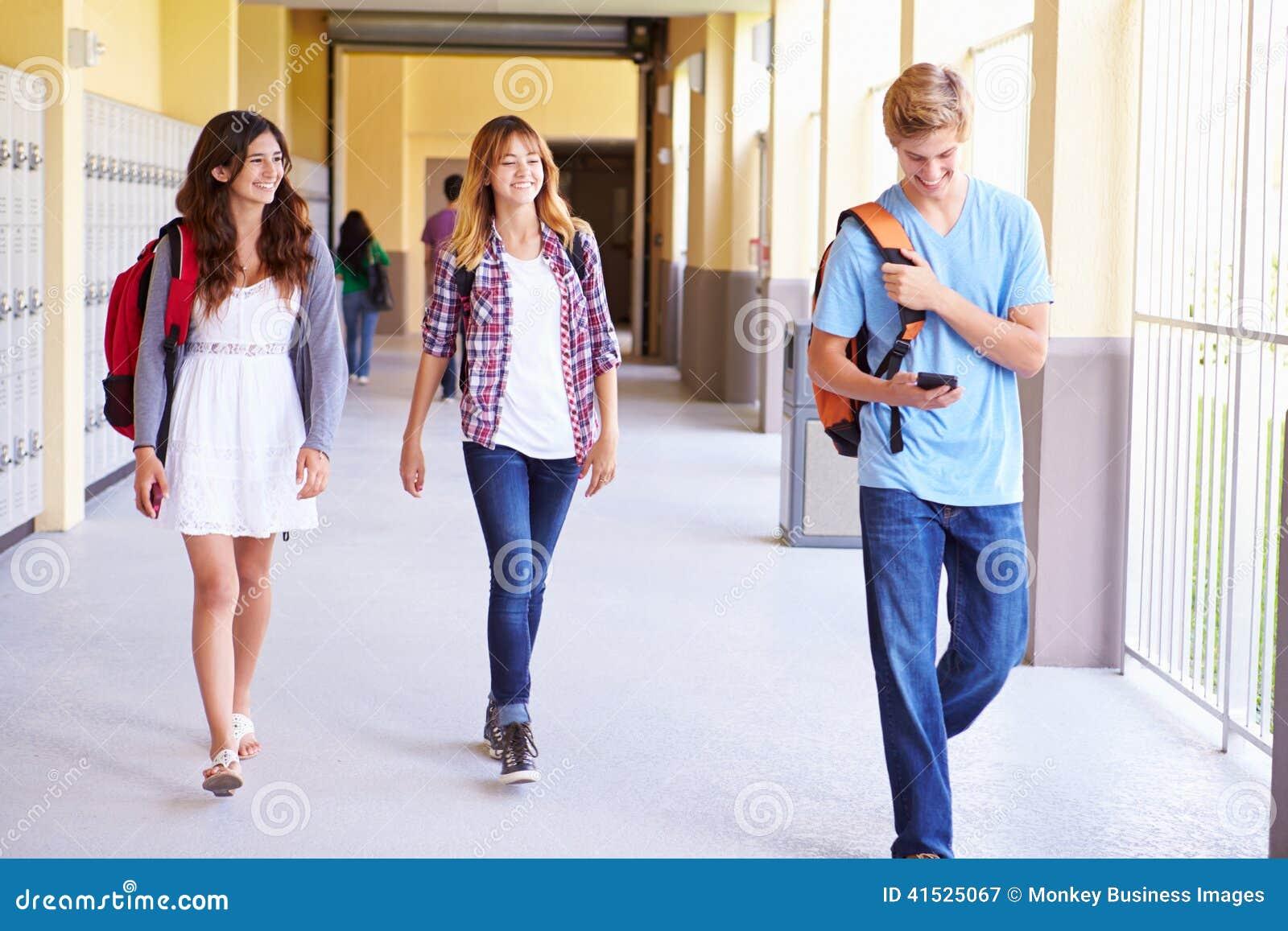 Estudantes da High School que andam no corredor usando o telefone celular