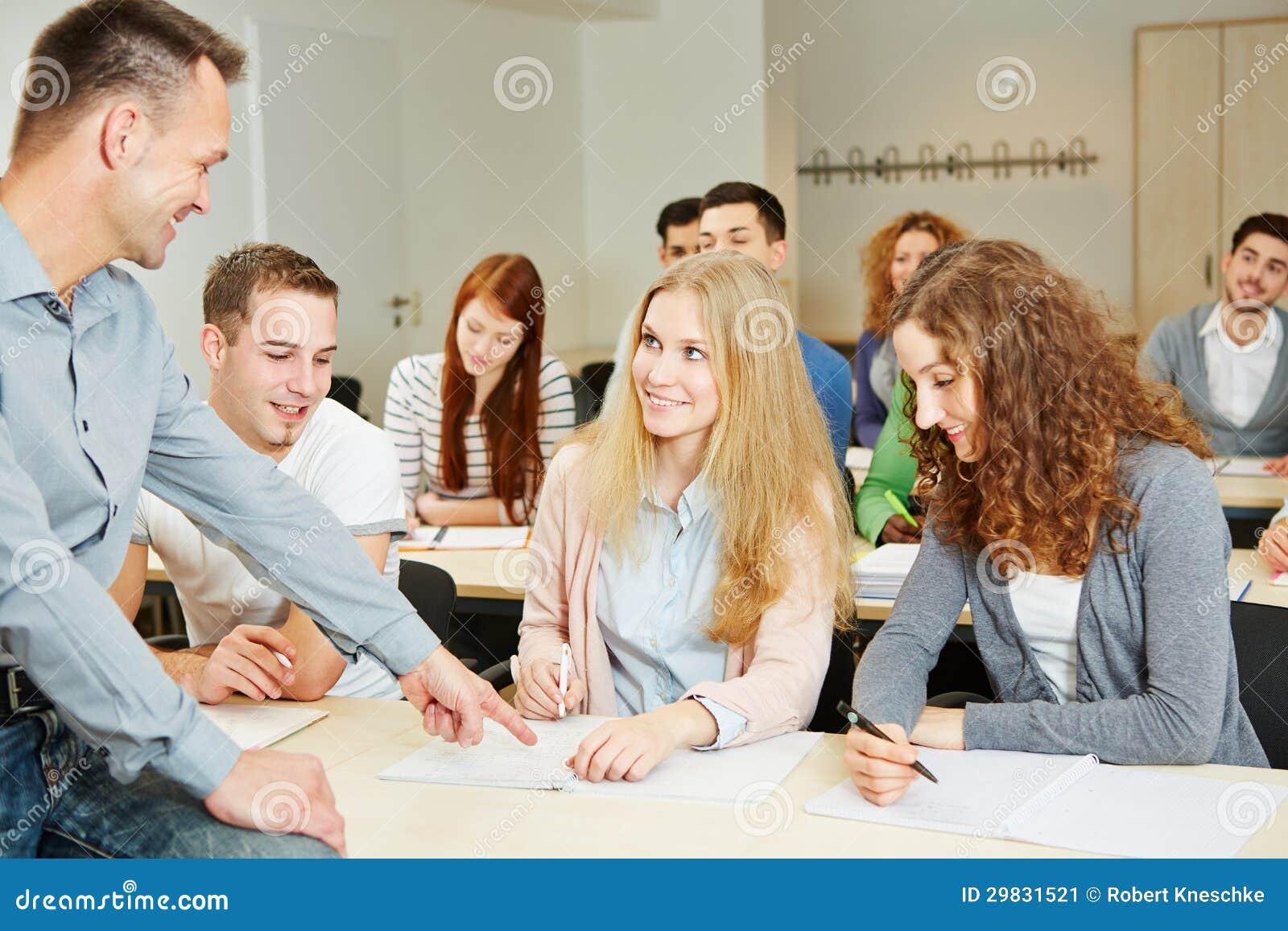 Estudantes de ajuda do professor na classe da universidade