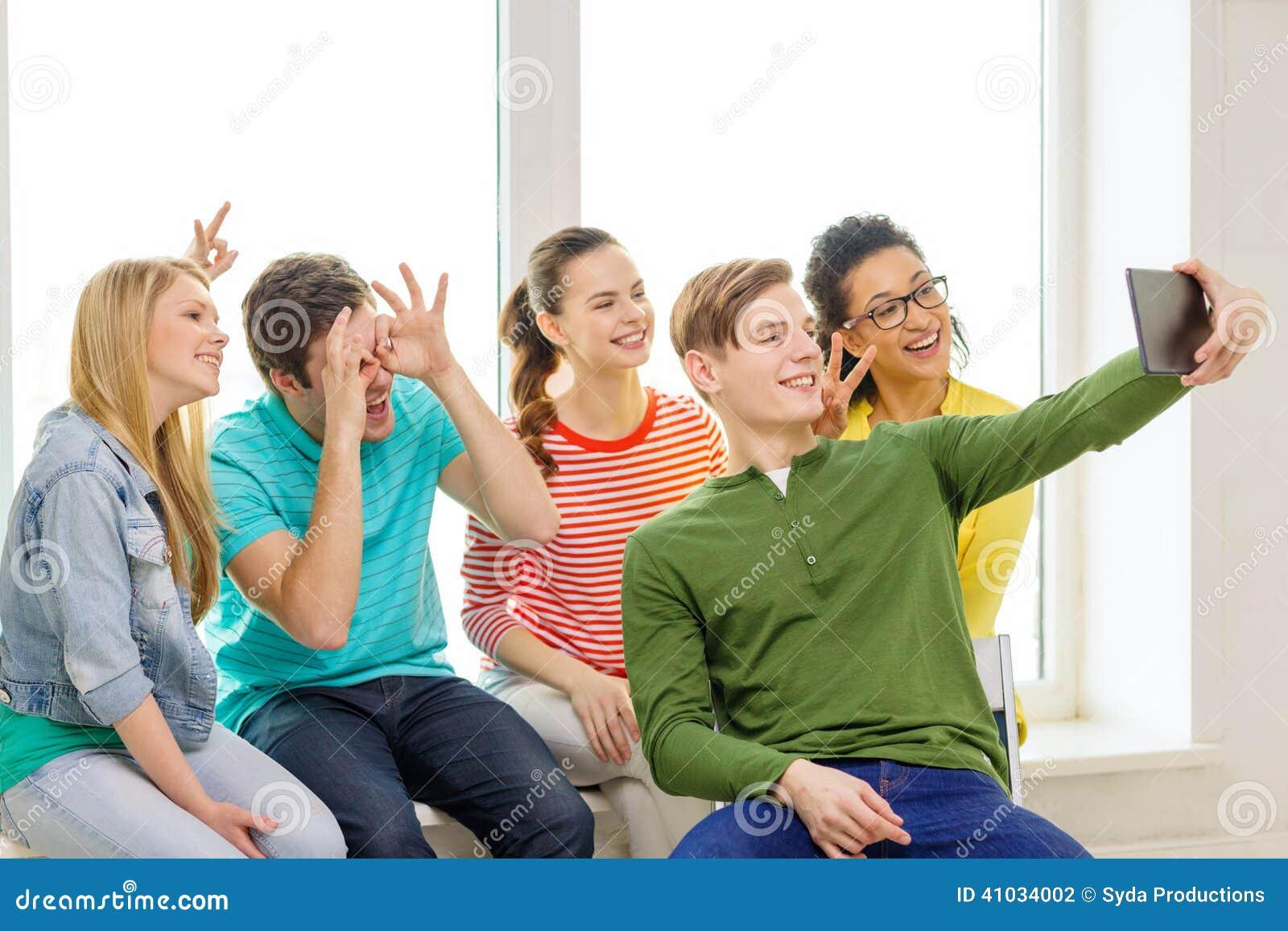 Estudantes de sorriso que fazem a imagem com PC da tabuleta