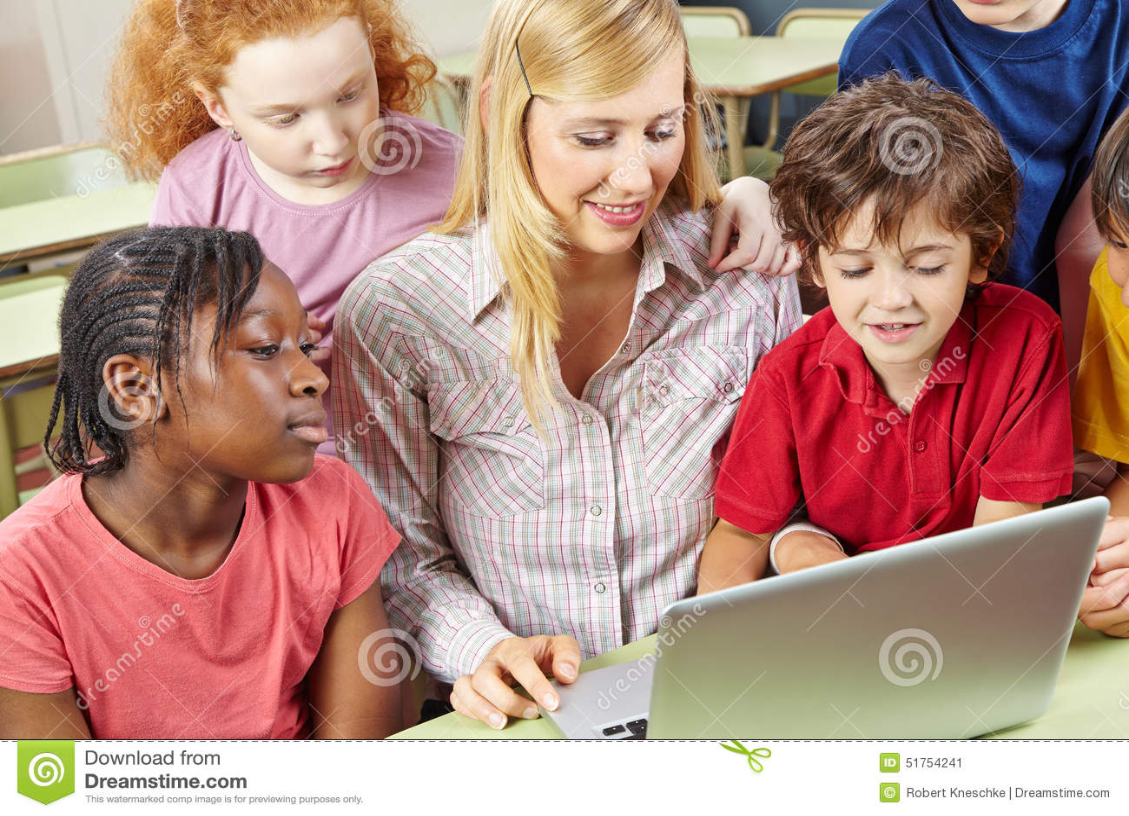Estudantes e professor que trabalham com laptop