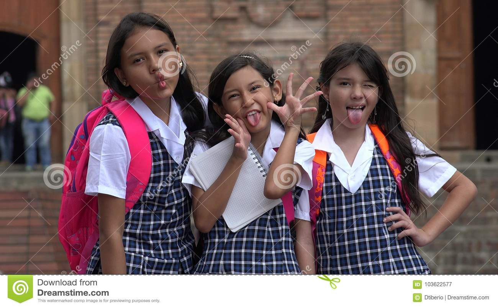 Estudantes fêmeas latino-americanos parvos que vestem fardas da escola