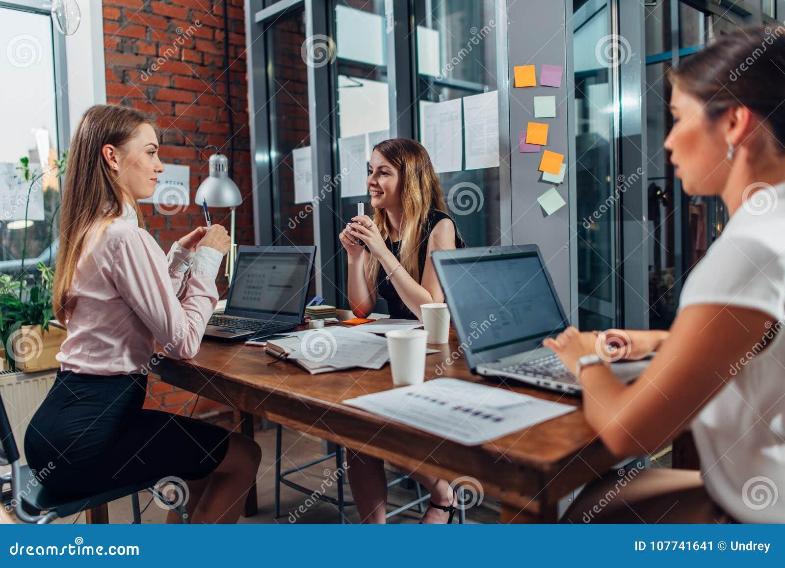 Estudantes fêmeas que trabalham na atribuição de escola usando os portáteis que sentam-se na mesa em uma sala de estudo