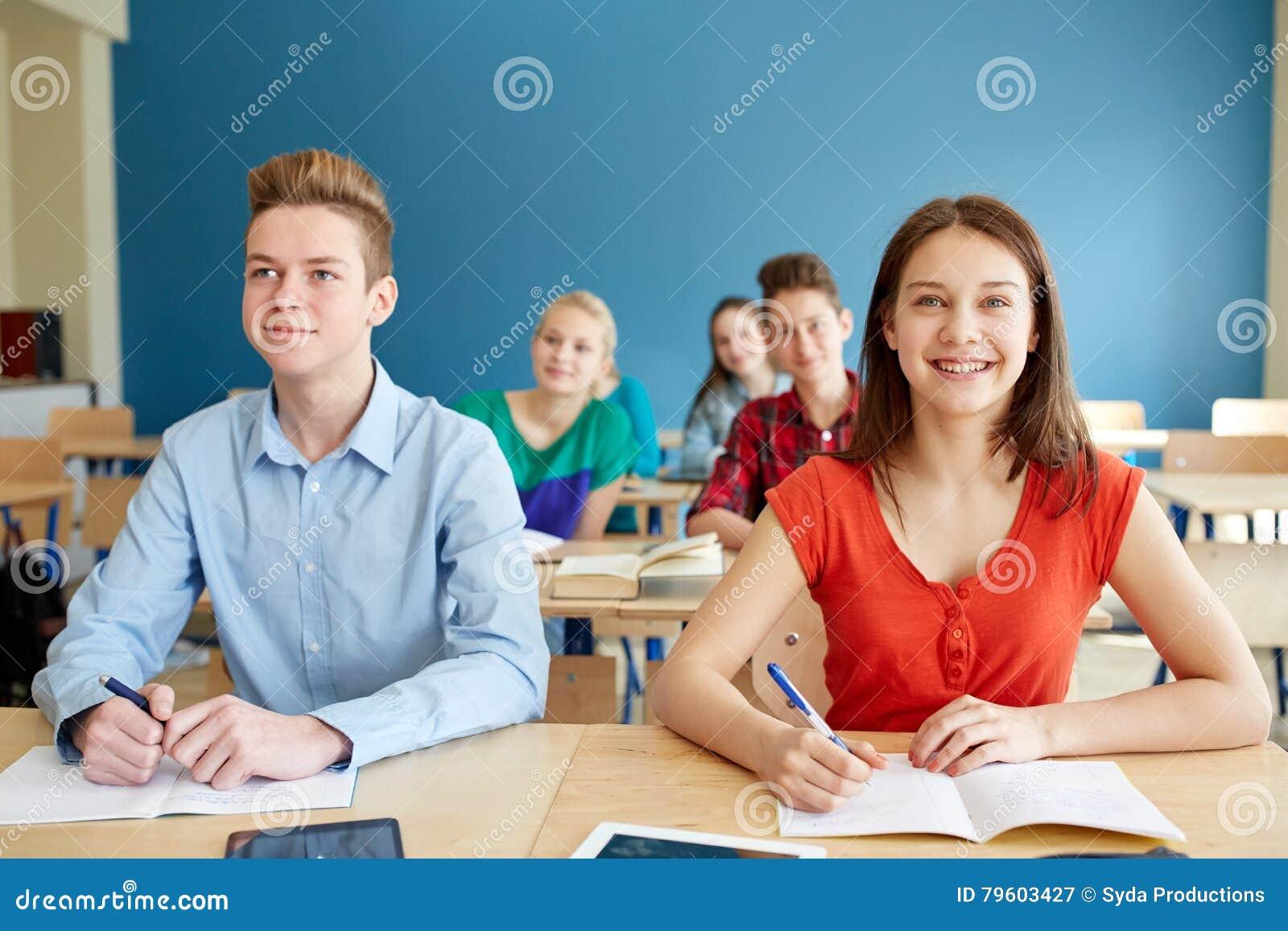 Estudantes felizes com os cadernos na escola