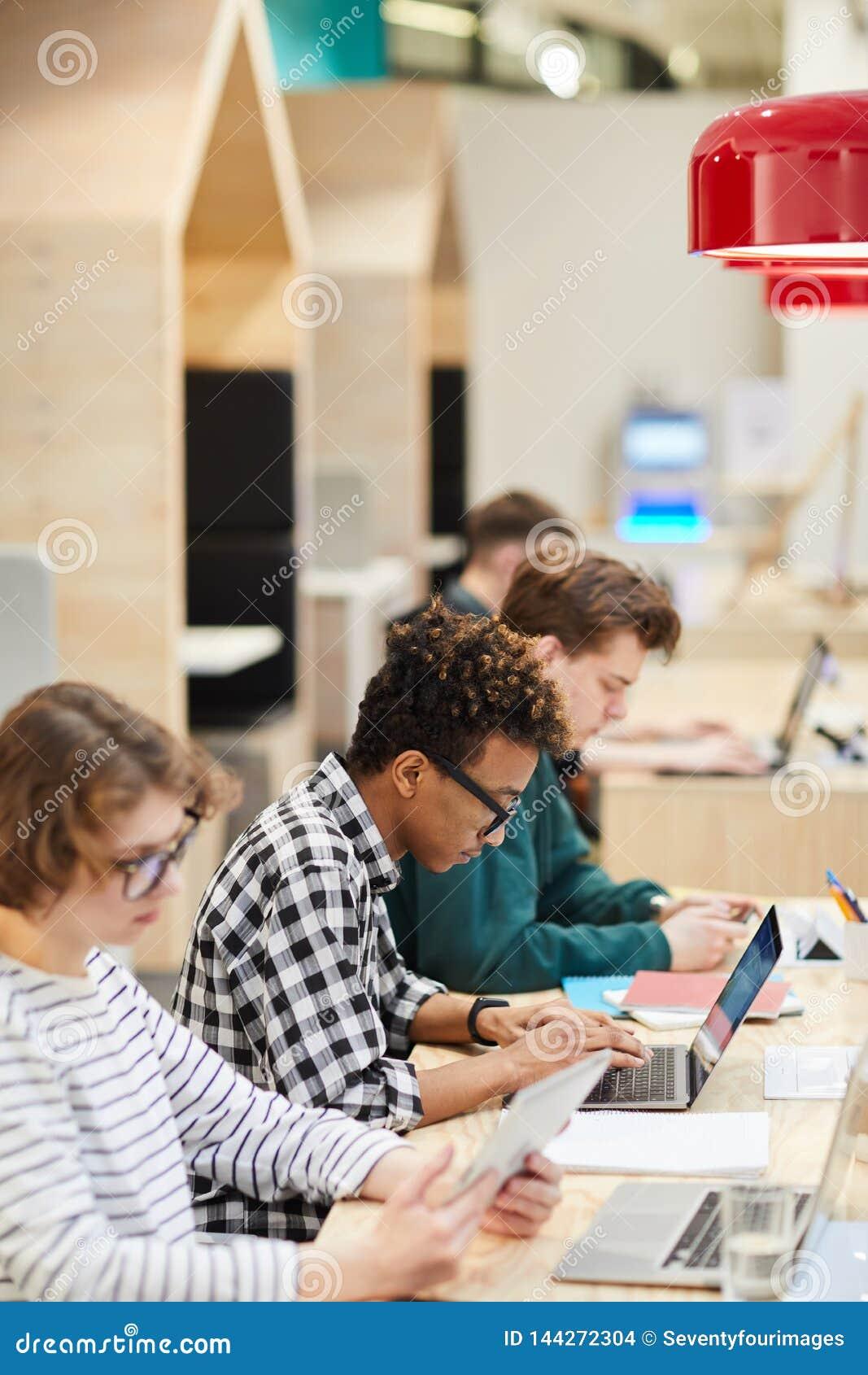 Estudantes na linha que faz o hometask na biblioteca