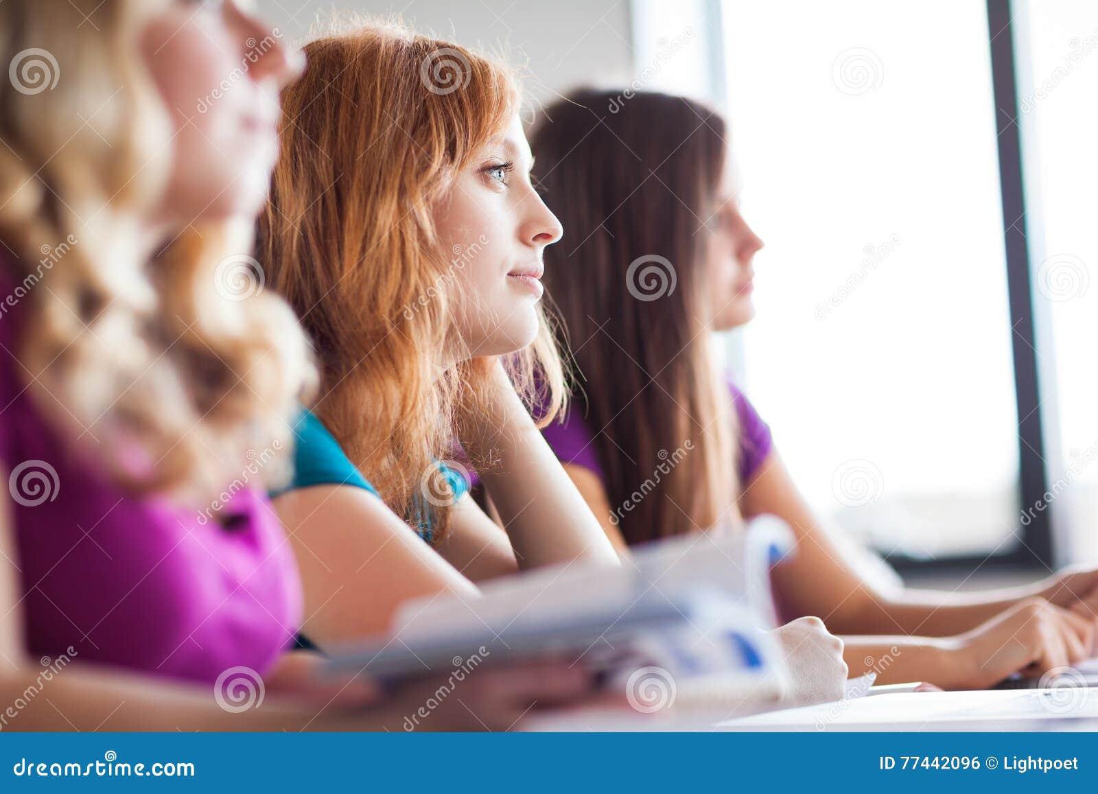 Estudantes na sala de aula - estudante universitário consideravelmente fêmea dos jovens