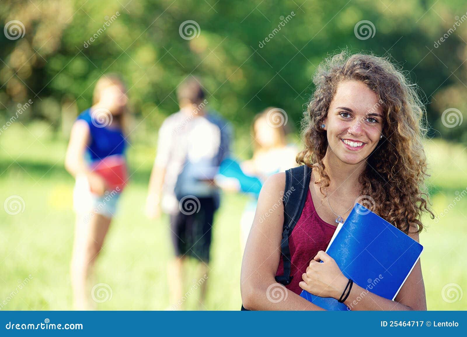 Estudantes novos felizes do retrato no parque