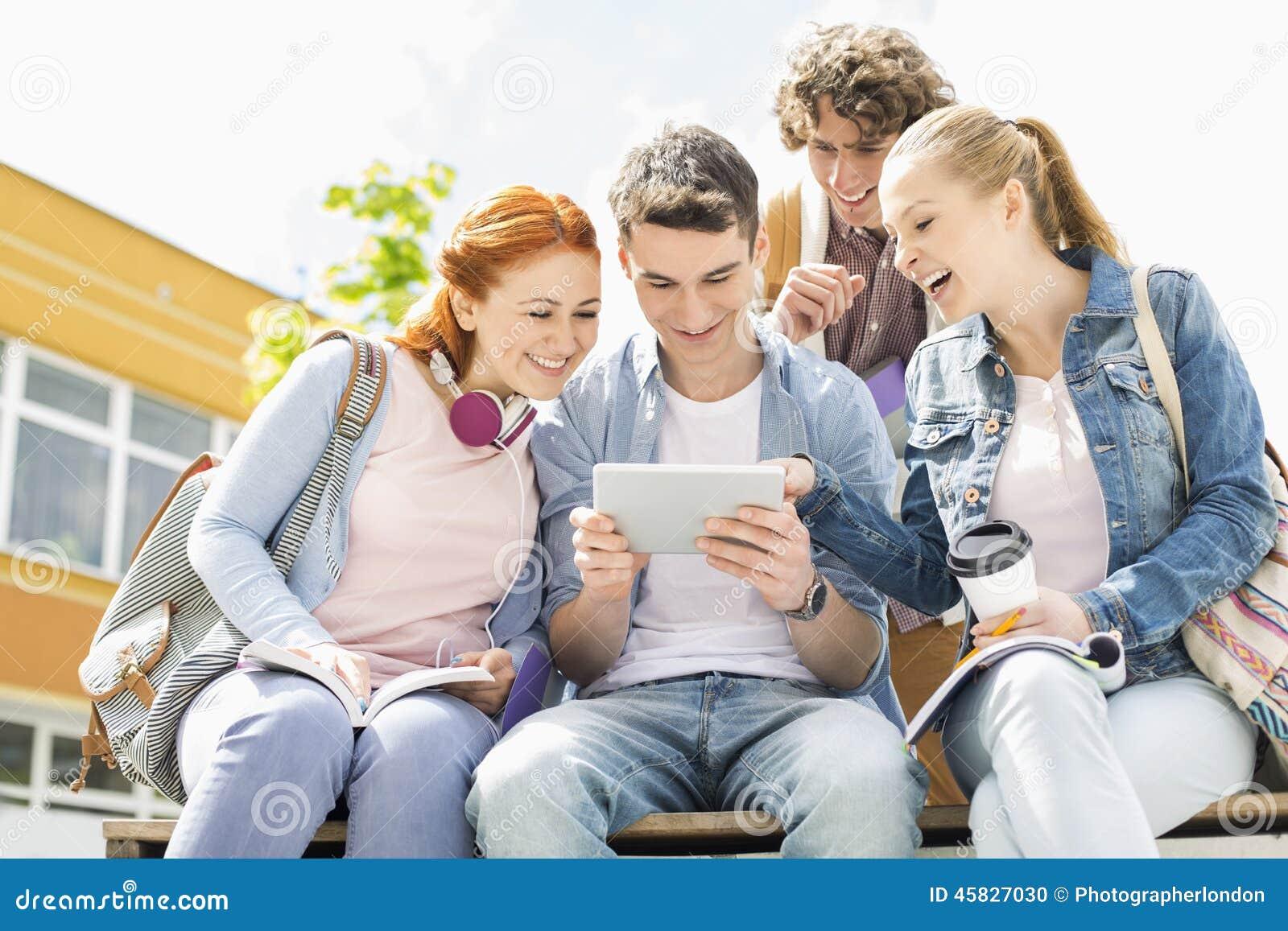 Estudantes novos que usam a tabuleta digital no terreno da faculdade