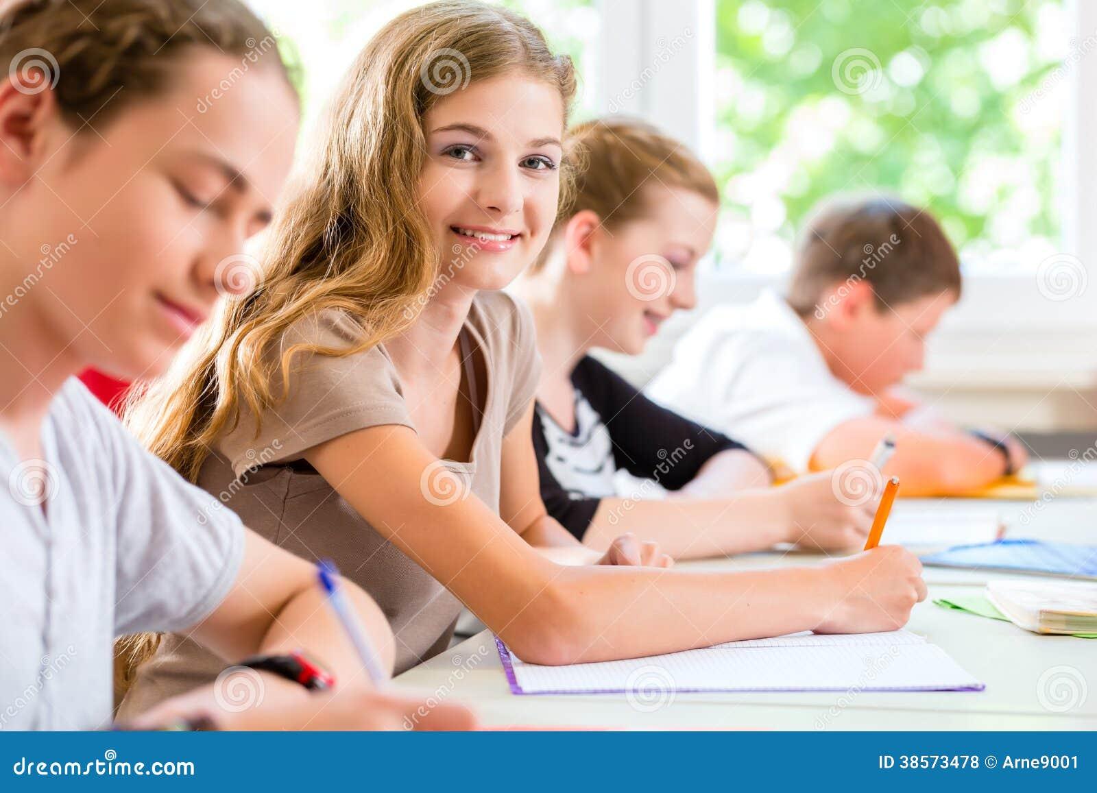 Estudantes que escrevem um teste na concentração da escola